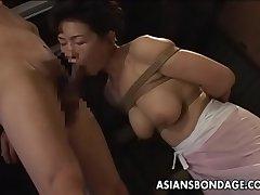 Bound Japanese MILF sucks surpassing a hard cock
