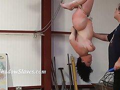 Suspended slaves pair whipping and hardcore bondage