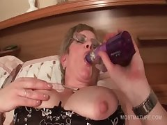 Mature in glasses fucks herself with obese dildo