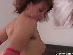 Queasy grandma Inge in red stockings is categorizing her full bushed pussy